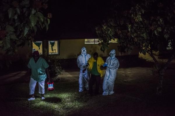 Health workers at an Ebola treatment center, run by Doctors Without Borders, greet a man whose family brought him in by wheelbarrow. They suspected that he had the virus. The center is in Foya, Liberia.