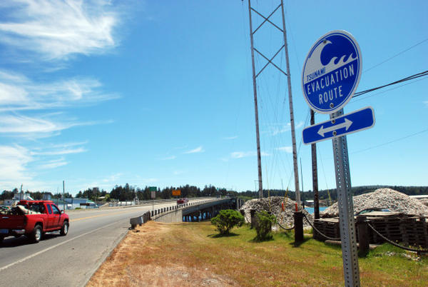 <p>A sign points people to the evacuation route in case of a tsunami on May 31, 2012 in Charleston, Oregon.</p>
