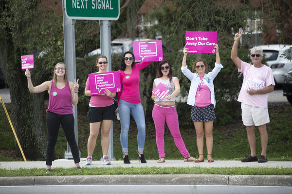 "Planned Parenthood supporters participate in ""Pink Out Day""  in front of the Tampa Health Center Tuesday."