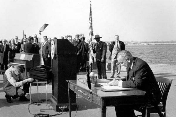 President Lyndon B. Johnson sits at his desk on Liberty Island in New York Harbor as he signs a new immigration bill on Oct. 3, 1965.