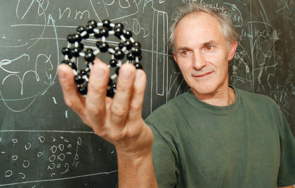 Kroto displays a model of his discovery in 1996: a soccer ball-shape carbon molecule that spawned a new field of study and could act as a tiny cage to transport other chemicals.