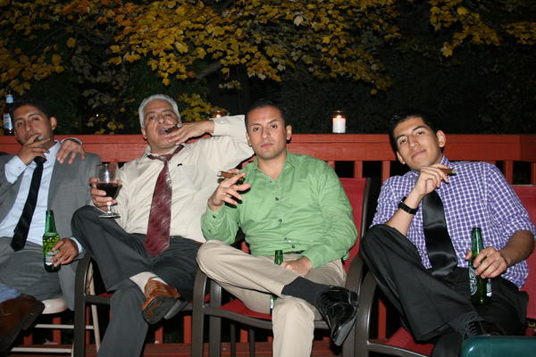 Victor Alarcon Sr. smokes a cigar with his three sons Alvaro (left), Victor Jr. and Miguel. The elder Alarcon emigrated from Bolivia in the 1980s.