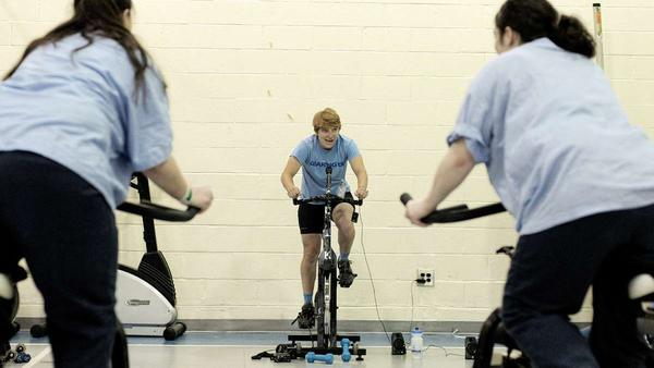 Instructor Erica Tibbetts uses a portable audio system to provide a soundtrack for the spinning class.