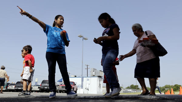 A volunteer with the Koch-funded Libre Initiative directs people in 2014 as groceries are distributed at a food bank it partially sponsors in San Antonio.