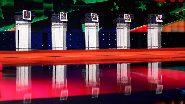 Photographs of Democratic presidential candidates hang on their debate lecterns before before the Democratic debate in Las Vegas Tuesday.