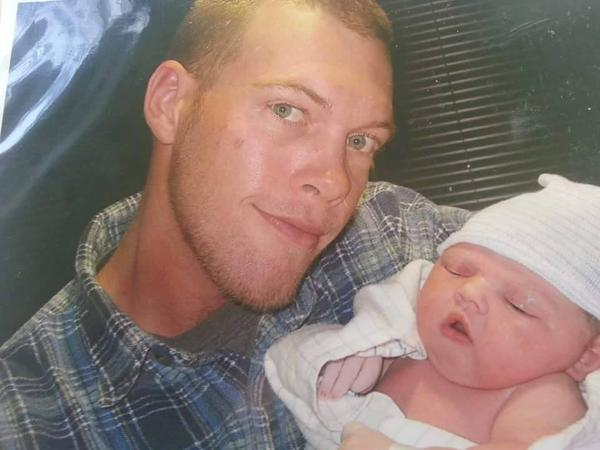 Billy Doyle Walker with his daughter, Kaylee, on the day she was born. Four months later, he died after falling from a tower he was painting. The opt-out plan his employer used provided his family with only a quarter of the benefits it might have received under the state's workers' compensation law.