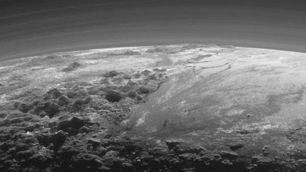 This image of Pluto, taken just 11,000 miles from the surface, reveals mountains of solid ice, against a hazy atmosphere.
