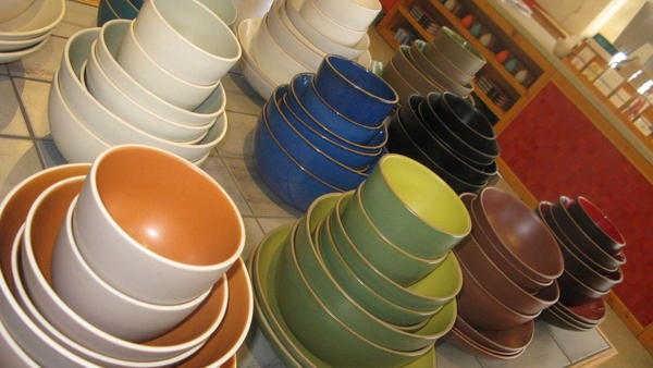 """Stacks of bowls in the company's signature colors, like """"sand"""" and """"light grey whale."""""""