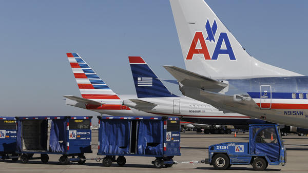 US Airways and American Airlines planes sit at the gates at Dallas/Fort Worth International Airport.