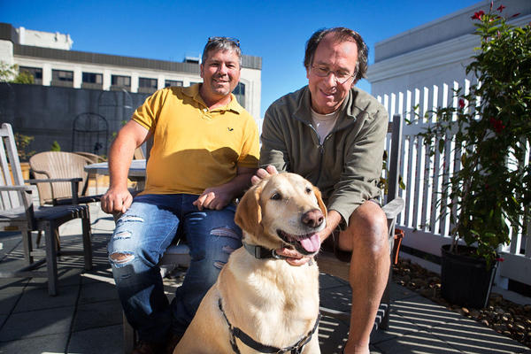 Dog rescuer Greg Mahle, left, sits outside WBUR with author Peter Zheutlin, who's written about Mahle's rescue efforts -- which include Zheutlin's dog Albie. (Jesse Costa/WBUR)