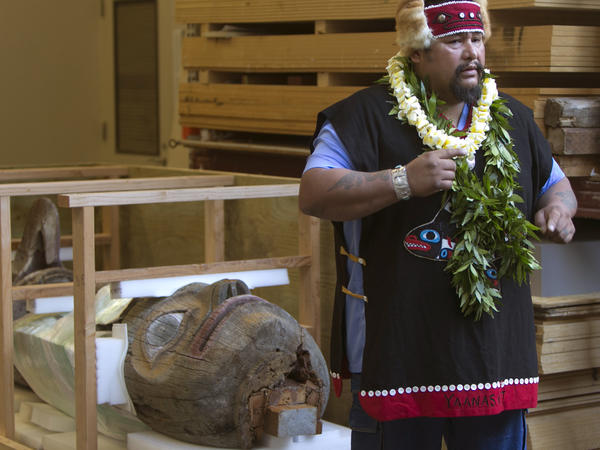 While standing in front of his tribe's totem pole, Jonathan Rowan speaks about its significance at the Honolulu Museum of Art on Thursday. The totem pole was carved by the ancestors of the Tlingit tribe. Rowan is a tribe member from Klawock, Alaska.
