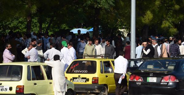 Pakistani federal employees gather outside their offices in Islamabad after Monday's deadly magnitude 7.5 earthquake.