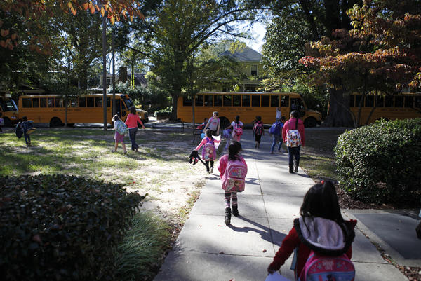 The end of the day at Watts feels like a party in front of the school. Some students rush to board buses while parents and teachers mingle.