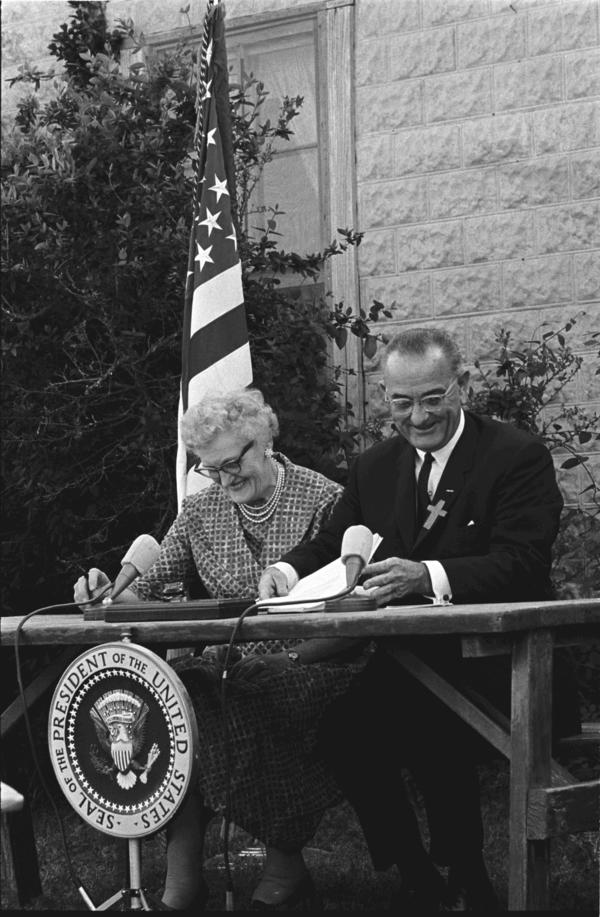 President Lyndon B. Johnson signs the Elementary and Secondary Education Act in 1965 with Kate Deadrich Loney, his first schoolteacher.