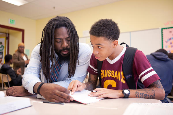 Mentor Antwon Cooper (left) helps student Julius Barne, 15, during a group activity in a history class.