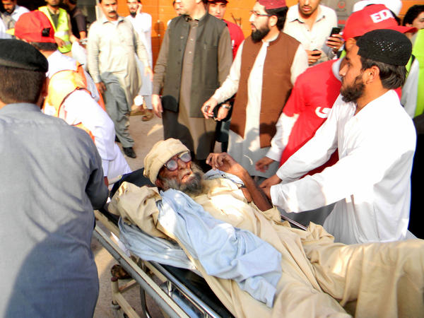 In Peshawar, Pakistan, people transfer an injured man to a hospital after a severe earthquake injured hundreds of people and caused more than 250 deaths across the region.