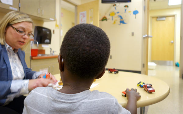 A young boy talks with Tina Cloer, director of the Children's Bureau, in Indianapolis. The nonprofit shelter takes in children from the state's Department of Child Services when a suitable foster family can't be found. Cloer says the average length of stay at the shelter has increased from two days to 10 in 2015.