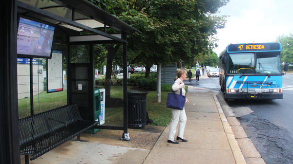 Mary Lee Kingsley waits for a bus in Montgomery County, Md. The bus stop has a big LED screen with a map displaying the current location of buses and when they will arrive.