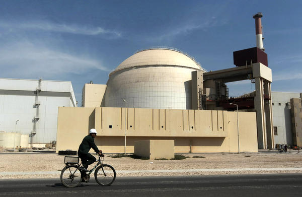 A worker rides a bicycle in front of the reactor building of the Bushehr nuclear power plant in southwestern Iran. After the 1979 Islamic Revolution, the ruling clerics initially said they had no use for a nuclear program. Ayatollah Khomeini said the silos at the Bushehr facility should be used to store wheat.