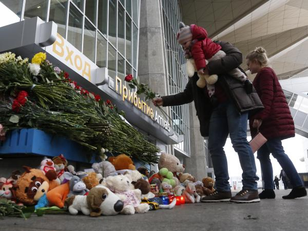 A family leaves flowers and toys at an entrance of Pulkovo airport outside St. Petersburg, Russia, during a day of national mourning for the plane crash victims.