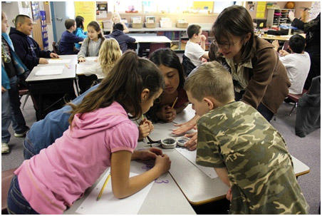 Frannie Smith on a 2012 visit to Finley Elementary School, demonstrating geologist's tools to third graders as part of a virtual fossil hunt.