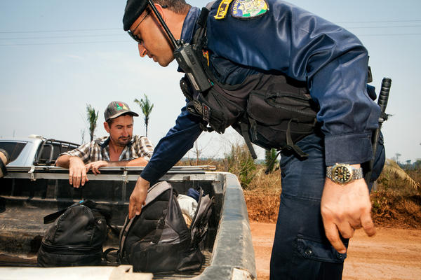 The environmental authorities, working in a convoy that consists of large pickup trucks, stop passersby and inspect their cars for signs of illegal activity.