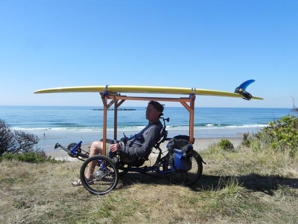 Ed Gunderson built a surfboard rack for his recumbent tricycle, which he's riding here on Beverly Beach in Oregon.