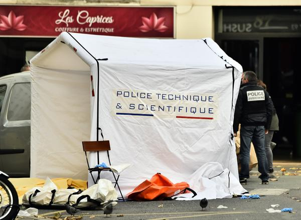A covered body lies by a forensic studies tent at the Rue de Charonne in Paris early Saturday morning, following a series of coordinated attacks in and around the capital on Friday, which resulted in at least 120 casualties.