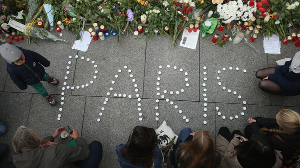 Mourners arrange candles at the gate of the French Embassy in Berlin. Hundreds of people came throughout the day to lay flowers, candles and messages of condolence to mourn the victims of attacks Friday night in Paris.