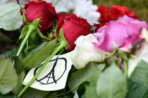 Flowers and a Peace for Paris sign sit outside the French Embassy in the Belarusian city of Minsk on Saturday.