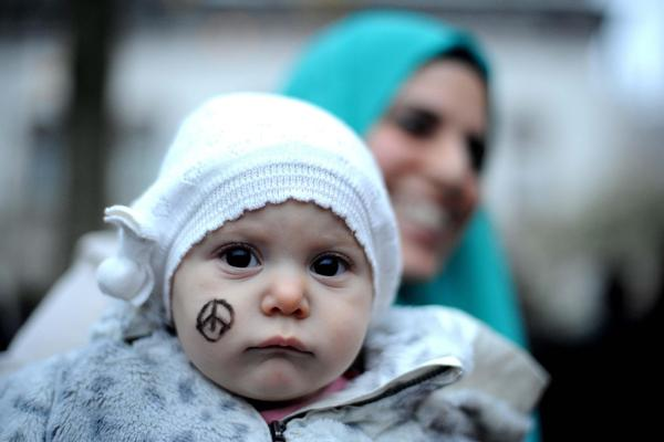 A baby wears the Peace for Paris symbol on her cheek, as people gather in a solidarity rally in Milan, Italy, on Saturday.