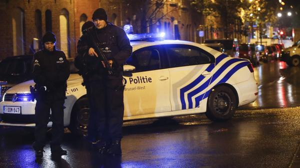 Police officers investigate the scene in the streets of Molenbeek, Brussels, Belgium, on Saturday. Officials say a man has been arrested in in connection with the terrorist attacks in Paris.
