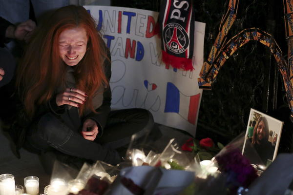 Polina Buckley, the girlfriend of Eagles Of Death Metal's merchandise manager Nick Alexander, who died in attacks in Paris, cries as she sits near a makeshift memorial outside the consulate of France in New York.