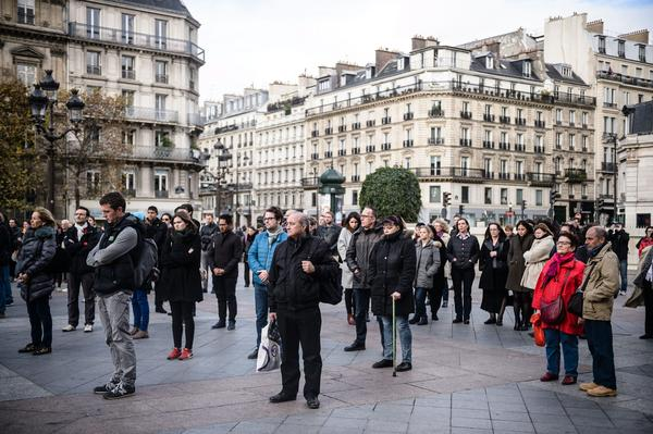 People gather to hold a minute of silence in front of the Paris city Hall, France, on Monday.
