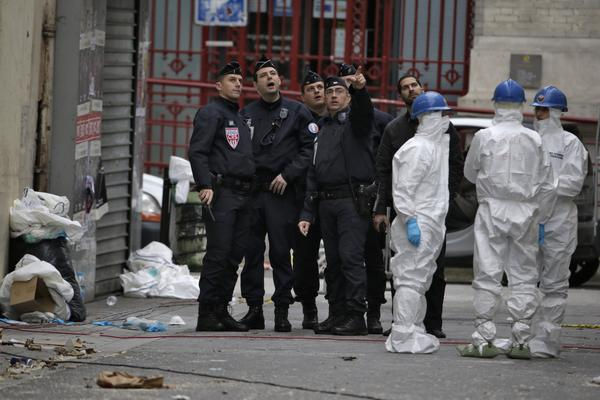 Forensics of the French police are at work outside a building in the northern Paris suburb of Saint-Denis, on Thursday, where French Police special forces raided an apartment the day before.