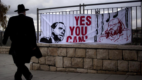 An Israeli man walks past a banner in 2013 depicting President Obama and Jonathan Pollard, a Jewish-American who was jailed in 1985 on charges of spying on behalf of Israel. Israelis have repeatedly called for Pollard's release. He is expected to be freed from a North Carolina prison on Friday.