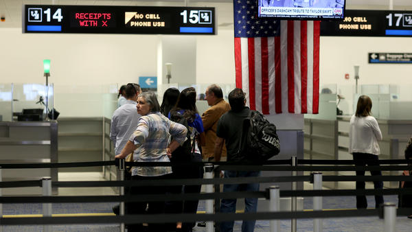 Passengers wait to get their passports checked at Miami International Airport earlier this year. The visa waiver program allowed 20 million travelers into the U.S. last year, with much less screening than refugees receive.
