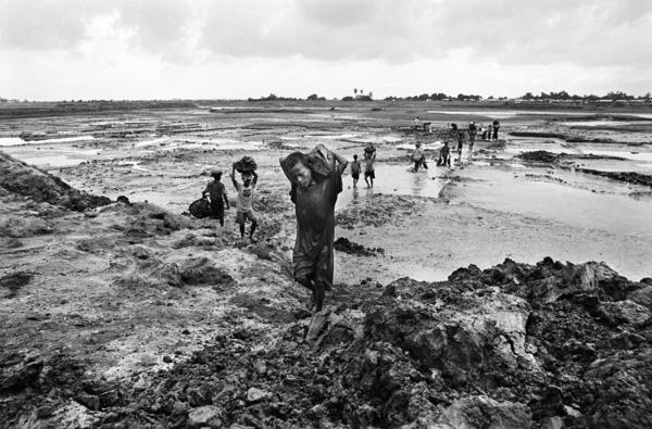 An estimated 1 million people from the Rohingya community are stateless in Myanmar. Here, 7-year-old Nur hauls mud with Rohingya men at a work site near one of the camps where they live.