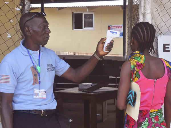 A relative of a boy who tested positive for Ebola in Liberia last week gets her temperature taken as she enters the clinic where he was being treated.