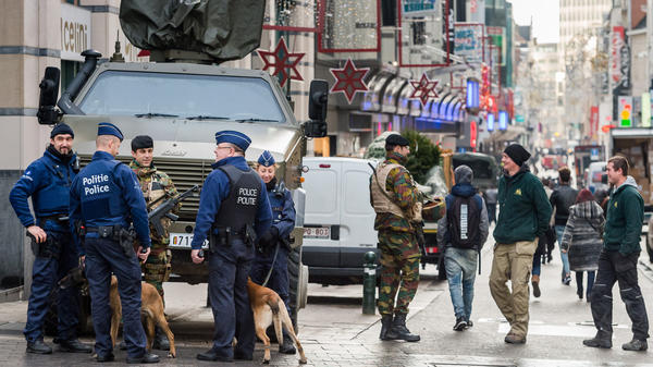 Army soldiers and police patrol a street in the center of Brussels on Wednesday. Students are returning to class after a shutdown over fears that a series of simultaneous attacks could be launched around the Belgian capital.