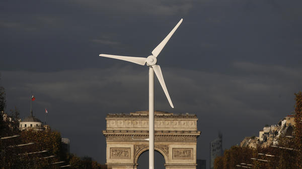 A power-generating windmill turbine is seen in front of the Arc de Triomphe on the Champs Elysees avenue in Paris ahead of the COP21 World Climate Summit, which begins Monday.