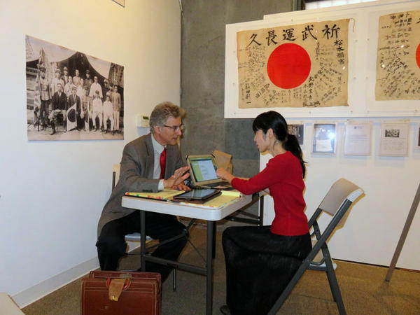 Trip organizers Rex and Keiko Ziak attend to last-minute details while simultaneously opening an exhibit on yosegaki hinomaru flags in Portland last week.