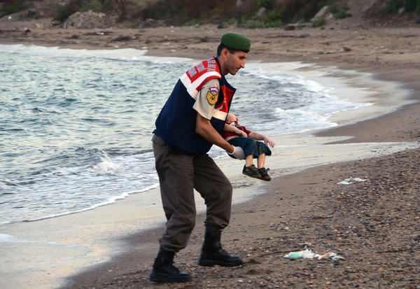 A Turkish paramilitary police officer carries the body of 3-year-old Aylan Kurdi, found washed ashore near the Turkish resort of Bodrum early Wednesday. The boats carrying the boy's family to the Greek island of Kos capsized. His 5-year-old brother and mother also lost their lives.