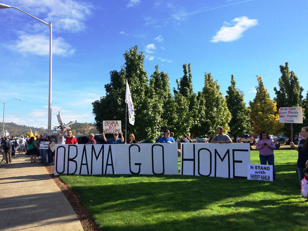 Protesters gathered outside the airport in Roseburg, Oregon ahead of President Obama's visit.