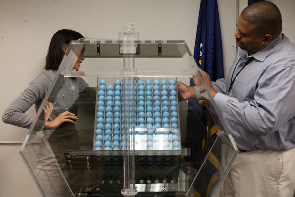 Selective Service program analysts Vince McClure (right) and Cristine Nguyen demonstrate the machines that would determine who would be drafted if the U.S. reinstates a miliatary draft.