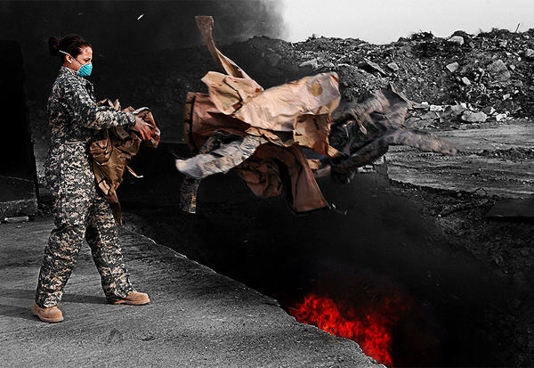 A U.S. airman tosses uniforms into a burn pit at Balad Air Base, Iraq, in 2008. The military destroyed uniforms, equipment and other materials in huge burn pits in Iraq and Afghanistan. Some veterans now say those pits are responsible for respiratory problems they are now experiencing.
