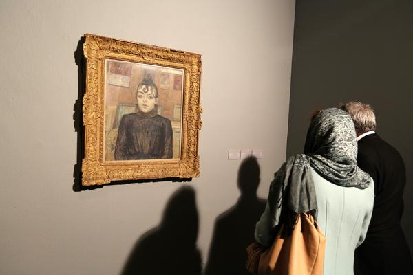 """Visitors look at the painting titled """"Girl with Lovelock"""" by French artist Henri de Toulouse-Lautrec at the opening of the exhibition."""