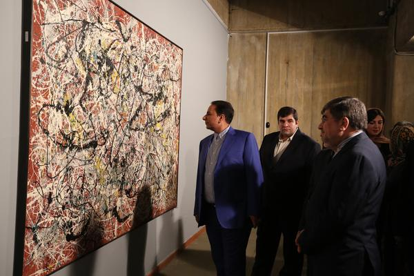 """Iranian Culture Minister Ali Jannati (right) looks at Jackson Pollock's """"Mural on Indian Red Ground"""" (1950) during the opening ceremony of an exhibition at Tehran's Museum of Contemporary Art on Nov. 20."""