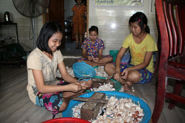 Girls prepare garlic to go in the mohinga at a Myaungmya Daw Cho restaurant in Yangon.