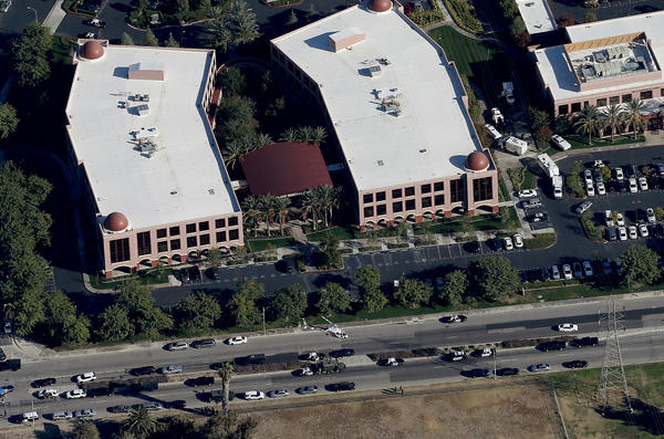 A police helicopter hovers around the Inland Regional Center in San Bernardino, Calif., the scene of a mass shooting on Wednesday.